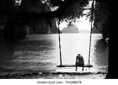 black and white of a man on the swing on the beach with islands background