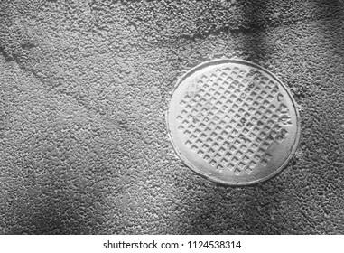 Black and white manhole in asphalt background