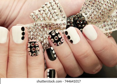 Black white manicure on a girl with actually and black dots close-up.