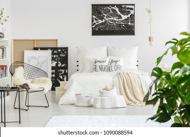 Black and white map poster hanging on the wall above bed in Nordic style room interior with diamond chair