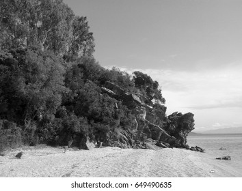 Black and white marine landscape. Dark cliffs on a pebble beach of the Pagasetic Gulf, Greece.