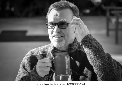 Black and white mature male drinks coffee telling story of head injury