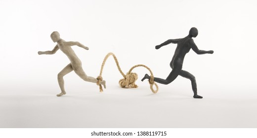 Black and white men run with a rope tied to the foot. Concept of the absurd escape. Isolated on white background. With space copy text. Shooting in studio.