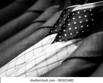 Black and white of men's shirts and suit hanging on rack.