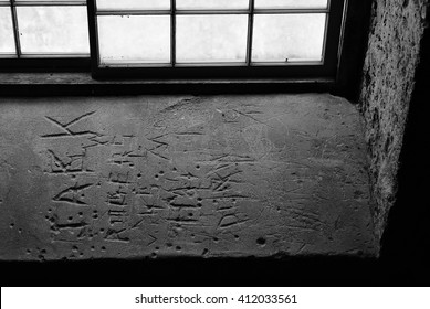 BLACK AND WHITE OF MESSAGES LEFT IN LIMESTONE WINDOW SILL