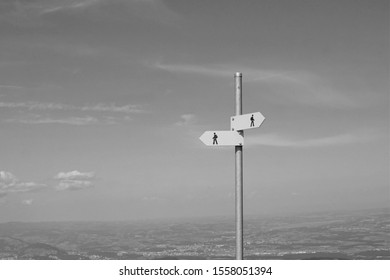 Black and white metal signpost displays two opposing directions of curving trail on mountaintop Small arrow signs point in direction for hikers walkers to go Sky distant cities landscape in background