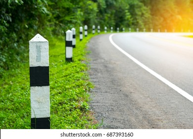 Black and white milestones with green grass roadside, Trees roadside in background . concept for next step. Next station.