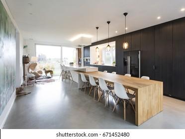 black & white minimalistic kitchen with wood details. concrete floor, composite white worktops.