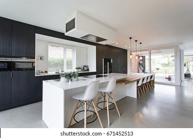 black & white minimalistic kitchen with wood details. concrete floor, composite white worktops.