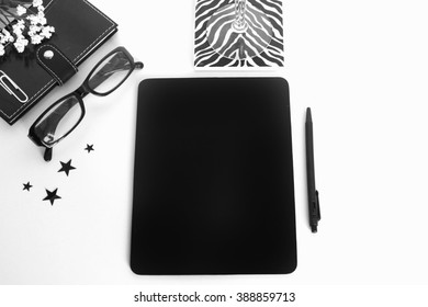 A black and white mock up desktop of a chalk board, glasses, zebra coaster, notebook, pen, white flowers and stars.