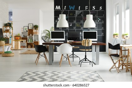 Black and white, modern coworking space with blackboard, desk, computer
