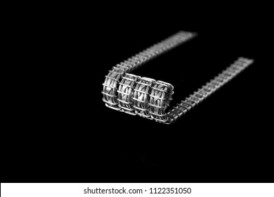 black and white, monochrome, close up, closeup, macro shot of framed staple twisted coil, fancy, art coil on black background, vape gear, vaping device, vaporizer equipment