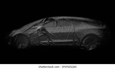 Black and white monochrome image with black background of side view of a car wrapped in grey protected cover