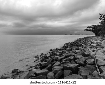 Black and white monochrome of rocky coastal beach with dramatic clouds