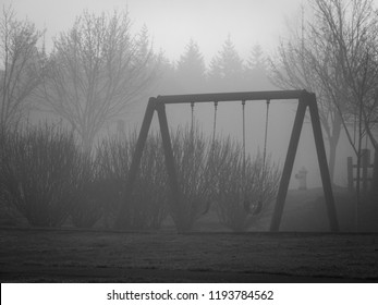 Black & White Moody Photo of an Empty Swingset on a Foggy Day in the Pacific Northwest, with Hazy Trees in the Background