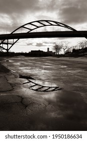 Black and White of Moody Sky and Hone Bridge Reflected in Puddle on Textured Pavement, Milwaukee Wisconsin