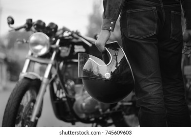 Black and white motorcycle, Biker wear jeans suit hold helmet and retro motorcycle background.