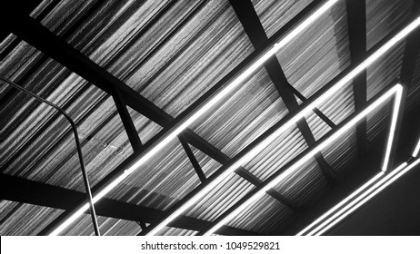 Black and white of neon lighting decoration under modern ceiling metal frame. Neon light bulb linear type illuminated background