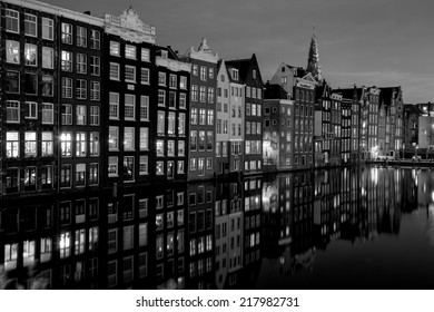 Black and white night shot of traditional houses in Amsterdam, capital of Holland, Netherlands,  with reflections in the canal