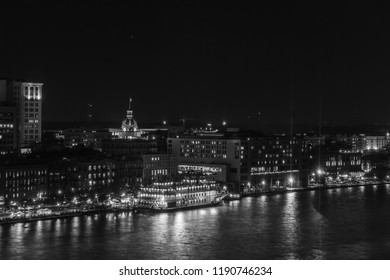 Black and White Night time view of Savannah at river street taken as an aerial view across the Savannah River with river boat lit up