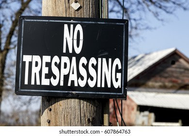 Black and White No Trespassing Sign in a Rural Area with a Barn in the Background
