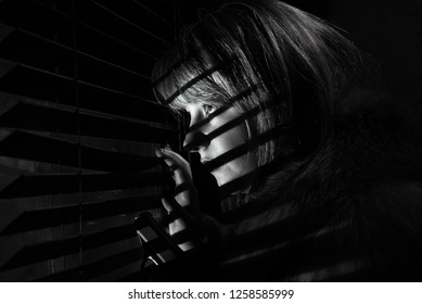 Black and white, Noir style image of a blonde female looking through window blinds.