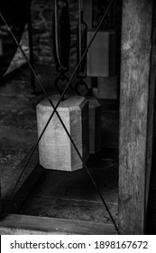 black and white old ancient European clock tower pendulum counterweight hanging from a pully by a rope mechanism timepiece details