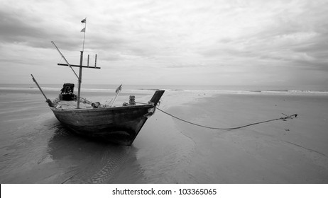Black and white: old wooden fishing boat landing on the beach