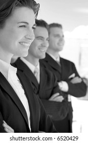 black and white one female two males wearing business suits in a row smiling