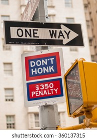 Black and white One Way sign and blue and red Don't Honk $350 Penalty sign at a crosswalk on a post in Manhattan, New York City, USA.