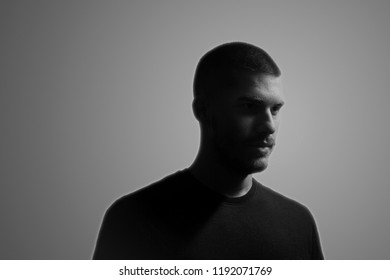 black and white, one young man, 20-25 years, moody dark portrait, side view. studio shot, gray background. head and shoulders shot.
