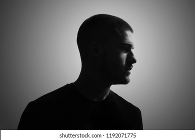 black and white, one young man, 20-25 years, moody dark portrait, profile. studio shot, gray background. head and shoulders shot.