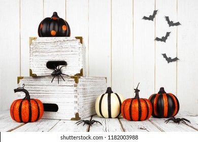 Black, white and orange Halloween decor against a white wood background