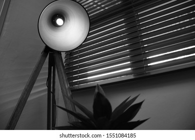 Black and white ornamental lamp with blinds in background