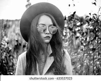 Black and white Outdoor fashion photo of young beautiful lady in autumn landscape with dry flowers. Gray coat, black hat, sunglusses, wine lipstick. Warm Autumn. Warm Spring