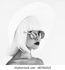 Black and white outdoor fashion photo of young beautiful lady in white hat and mirror sunglasses. Summer Beach travel. Summer vibes
