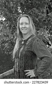 Black and white outdoor portrait of a natural looking blond woman.