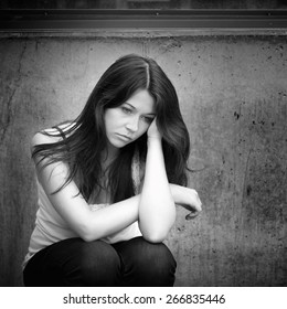 Black and white outdoor portrait of a sad teenage girl looking thoughtful about troubles in front of a gray wall
