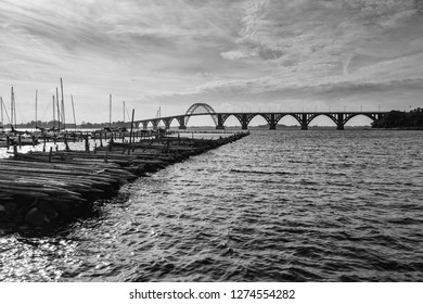 black and white panorama of the Moen-Bridge in Denmark with stakes at the marina of Kalvehave in the foreground