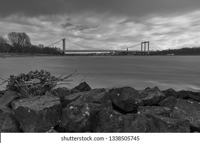 Black and White - Panorama on the Rhine with rocks in the foreground and view over the Rhine to the Rodenkirchen bridge. There are strong winds over the city.
