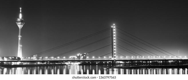 Black and white panorama with the Rheinturm and the Oberkasseler bridge.