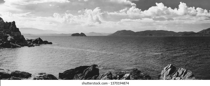 Black and white panorama of rocky beach with calm blue sea and sky in Phu Yen, Vietnam
