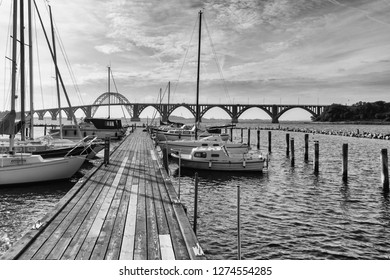 black and white panoramic view of the famous bridge of Moen in Denmark with the marina of Kalvehave in the foreground and a wooden pier leading the view into the picture