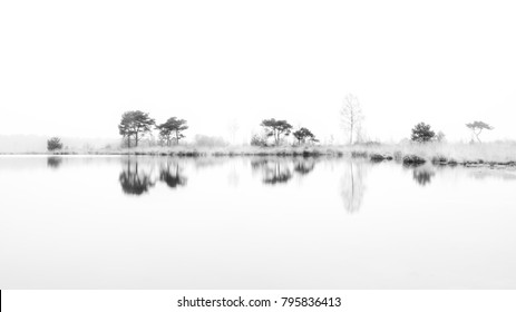 Black and White perfection. An almost whole white picture. Beautiful 'zen' scene. Horizon reflection in calm milk clear water.