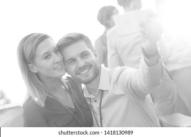 Black and White phot of Smiling young businessman taking selfie with businesswoman at party on rooftop