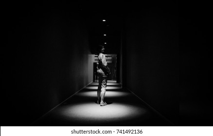 Black and white phot of a woman walking alone in an empty dark corridor in apartment building in perspective view with copy space. View of a dark creepy hall with a woman in the center.