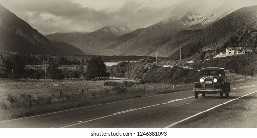 black and white photo of a 1920's car travelling along a remote road with a mountain backdrop