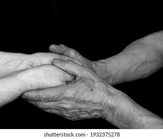 A black and white photo of an adult man and woman holding hands on a black background. Concept together forever. Elderly man and woman. Elderly couple holding hands