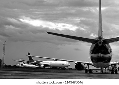 Black and white photo of aircraft and focus at tail cone of aircraft (airplane) parking in front of aircraft hangar for maintenance.