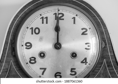 Black and white photo of an antique clock showing 12 oclock